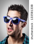 Young boy smiling with blue sunglasses. - stock photo