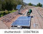 OAK VIEW - OCTOBER 10: Workers install solar panels on the roof of a house on October 10, 2011 in Oak View, Southern California - stock photo