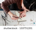 Bird eye view of a female jeweler working in her workshop. - stock photo