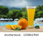 Glass of orange juice on a beach table - stock photo