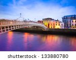 Dublin Ireland at dusk with waterfront and historic Ha'penny Bridge - stock photo
