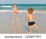 two happy kids playing on beach   Shutterstock . vector #133897397
