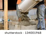 Worker working concrete on a post foundation support at a large commercial housing development in Oregon - stock photo