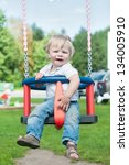 Swinging little boy - stock photo