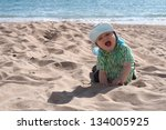 Happy baby boy on the beach - stock photo