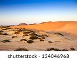 Sand dunes, mountains and scrub at sunset in the middle of the desert in Oman on Route 35 - the 'Dunes highway' - stock photo