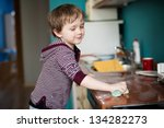 Boy cleaning the kitchen after making dinner - stock photo