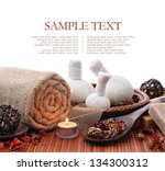 Spa massage setting with rolled, towel, compress balls and candlelight - stock photo
