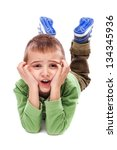 Upset little boy lying on the floor holding his face with both hands  isolated on white background - stock photo