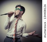 funny stylish businessman singing on gray background - stock photo