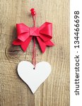 Red bow with a heart made of paper on a wooden background - stock photo