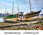 Wrecks of wooden ships anchored on an empty shore at the Atlantic Ocean. - stock photo