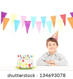 Smiling boy with party hat and a birthday cake isolated against white background - stock photo