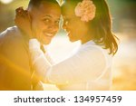 Beautiful couple embracing and caught in a rainbow of sunshine - stock photo