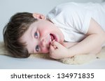 Cute young boy lying on floor watches television/computer for fun - stock photo