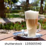 A tall glass containing latte coffee standing on a woorden table with a beautiful garden in the background - stock photo