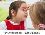 little girl doing make up to... | Shutterstock . vector #135013667