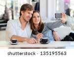 young woman taking a photo with ... | Shutterstock . vector #135195563
