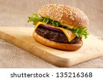 Homemade gourmet hamburger on wooden board - stock photo