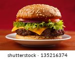 Homemade grilled hamburger on plate with red background - stock photo