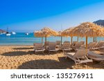 The sandy beach near the blue sea with sun beds and umbrellas. Mykonos - stock photo