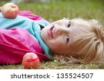 happy girl with apples lying on ... | Shutterstock . vector #135524507