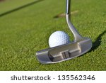 golf ball and putter on green - stock photo