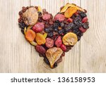 Dried fruits in the shape of hearts on a wooden background - stock photo