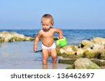 Baby Playing With Water In Sea