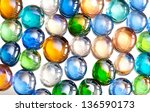 Small photo of Plenty agleam multicolored glass balls or marbles mix on white background, color beads with reflections, abstract in horizontal orientation, nobody.