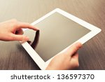 white tablet with a  blank screen in the hands on wooden table - stock photo