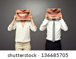 woman and man holding pictures with big smile. concept photo over dark background - stock photo