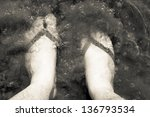 feet of the man in slates standing in water - stock photo