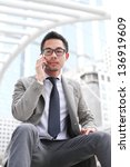 Asian business man speaking mobile phone - stock photo
