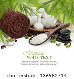 Spa massage border background with rolled towel, compress balls, stacked basalt stones, sea salt, and bamboo - stock photo