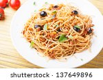 Spaghetti with tomato sauce and fresh basil leaves on white dish - stock photo