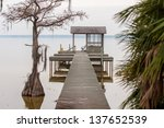 gazebo pier on a lake with chairs - stock photo