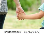 mother holding a hand of her son | Shutterstock . vector #137699177