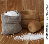 A bag of sea salt and a wooden mortar - stock photo