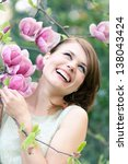 Spring portrait of a beautiful woman standing under a magnolia tree - stock photo