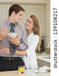 Small photo of Man eats cereal while parter is embracing him in kitchen