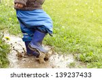 Child In Boots Jumping In Mudd...