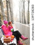 Two Young Girls Sitting On A...