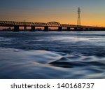 The Sun Sets Over A Bridge As ...