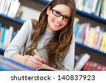 beautiful girl in a library  | Shutterstock . vector #140837923