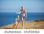 Stock photo beautiful woman with her dog playing on the sea shore outdoor portrait 141926563