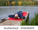 Stock photo full length of mature man lying on pier against lake 142636693