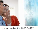 happy couple looking at modern... | Shutterstock . vector #143164123