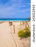 Small photo of Beach sand yellow flowers turquoise sea view, Cala Agulla, Majorca island, Spain
