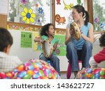 young teacher with girl playing ...   Shutterstock . vector #143622727